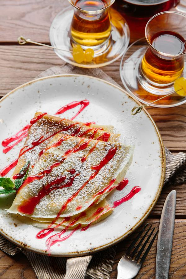 Delicious thin pancakes served with strawberry sauce on a wooden rustic table royalty free stock image