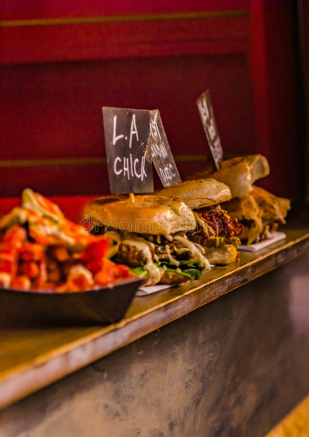 Delicious three burgers. With beef, pork and chicken and vegetables royalty free stock images