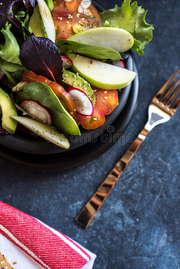 Delicious tomato and guacamole lettuce salad, with green apple and radish on dark background stock image