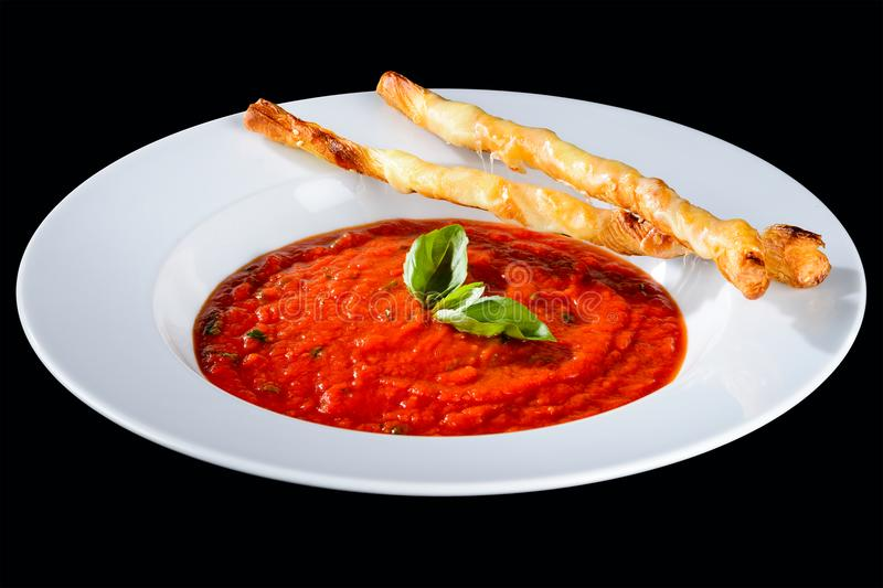 Delicious tomato soup decorated with basil and bread sticks isolated on dark background stock photos