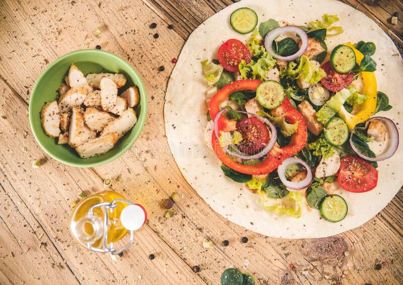 Delicious tortilla wraps on wooden table with vegetable royalty free stock photography