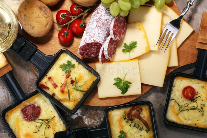 Delicious traditional Swiss melted raclette cheese on diced boil royalty free stock photography