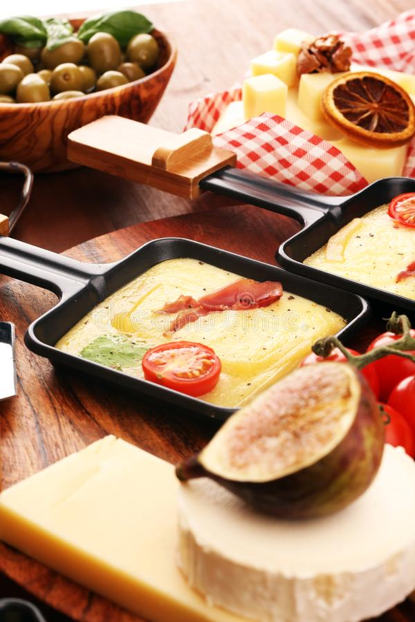Delicious traditional Swiss melted raclette cheese on diced boiled or baked potato and baguette served in individual skillets with stock image