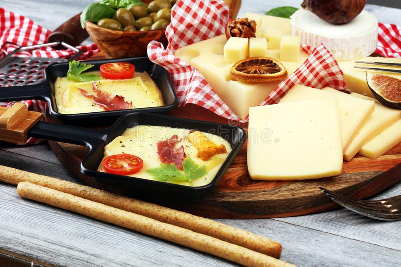 Delicious traditional Swiss melted raclette cheese on diced boiled or baked potato and baguette served in individual skillets with royalty free stock photo