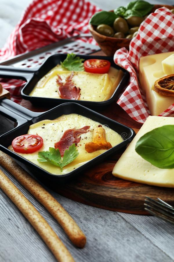 Delicious traditional Swiss melted raclette cheese on diced boiled or baked potato and baguette served in individual skillets with stock photos