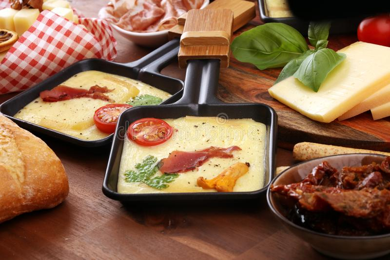 Delicious traditional Swiss melted raclette cheese on diced boiled or baked potato and baguette served in individual skillets with stock images