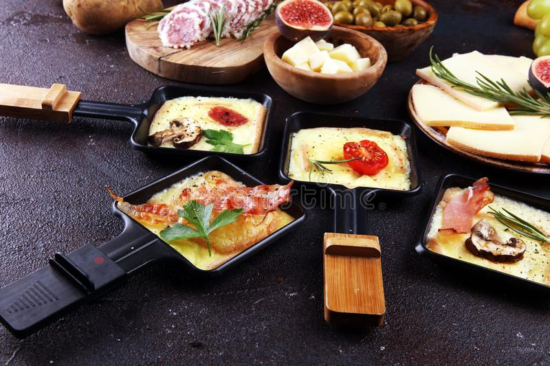 Delicious traditional Swiss melted raclette cheese on diced boiled or baked potato stock photos