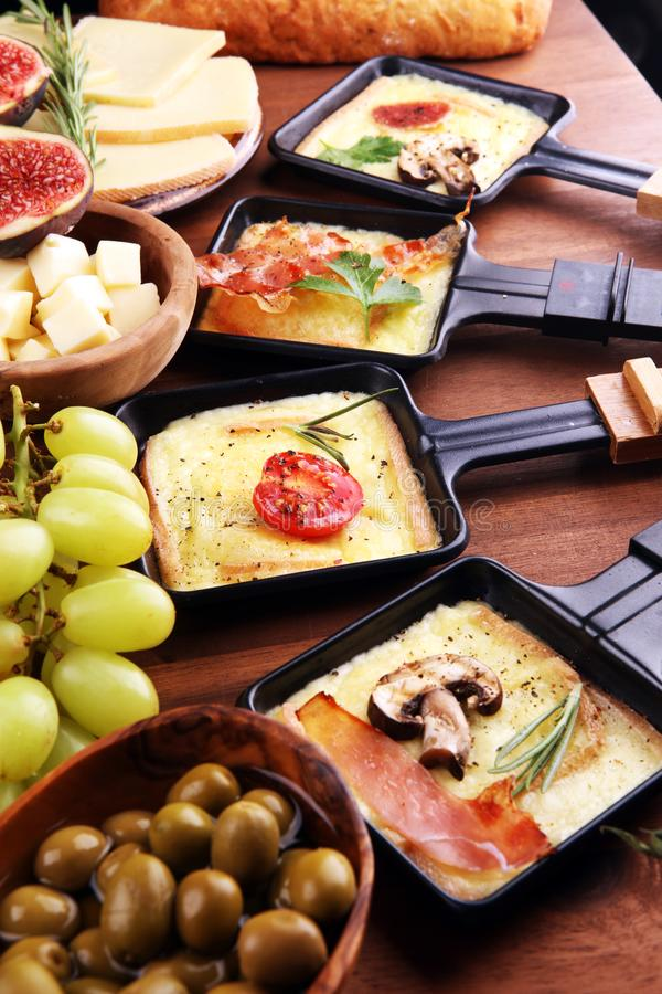 Delicious traditional Swiss melted raclette cheese on diced boiled or baked potato stock image