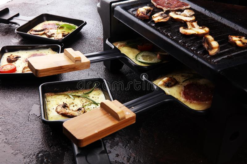Delicious traditional Swiss melted raclette cheese on diced boiled or baked potato stock images