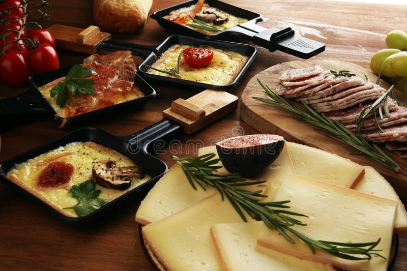 Delicious traditional Swiss melted raclette cheese on diced boiled or baked potato royalty free stock photos