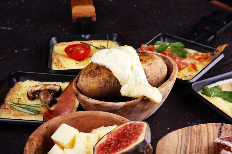 Delicious traditional Swiss melted raclette cheese on diced boiled or baked potato royalty free stock photo