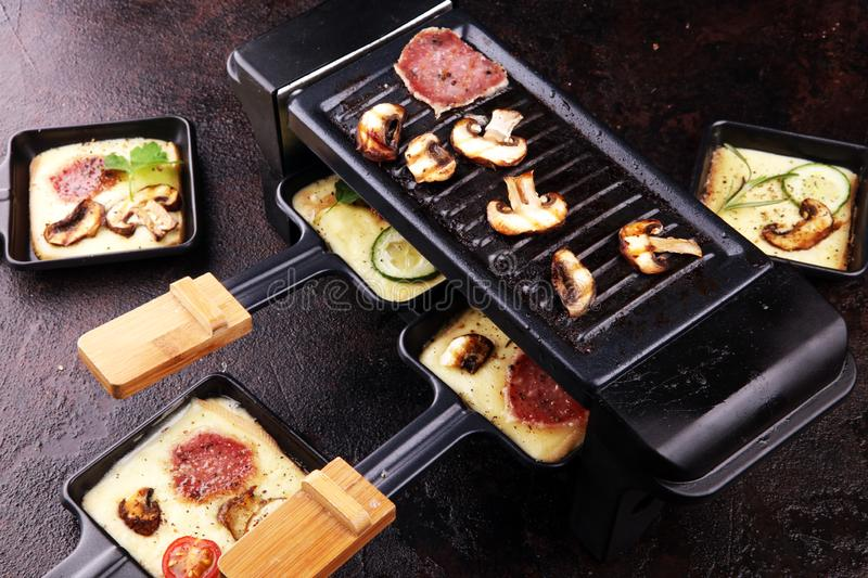 Delicious traditional Swiss melted raclette cheese on diced boiled or baked potato royalty free stock photography