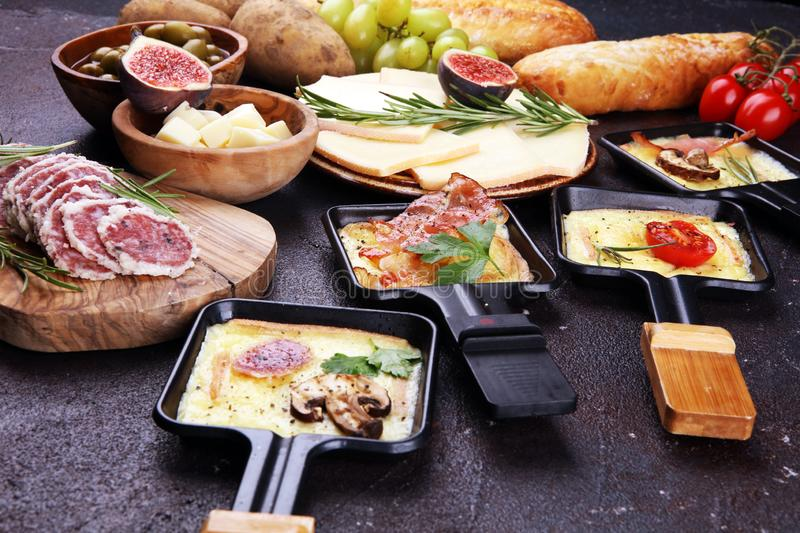 Delicious traditional Swiss melted raclette cheese on diced boiled or baked potato stock photography