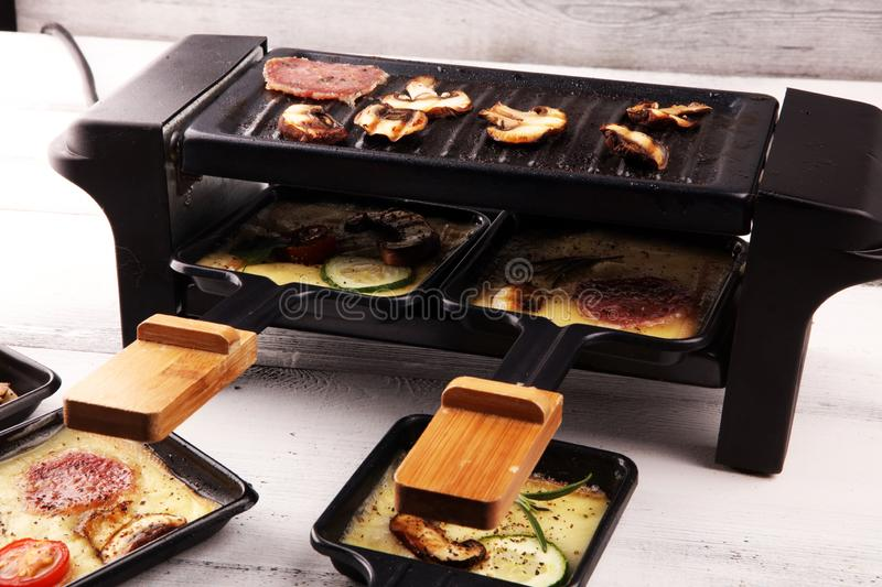 Delicious traditional Swiss melted raclette cheese on diced boiled or baked potato stock photo