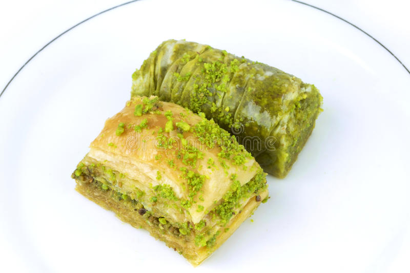 Delicious Turkish baklava and sarma with green pistachio nuts. Delicious Turkish baklava and sarma with green pistachio nuts on white background stock photo