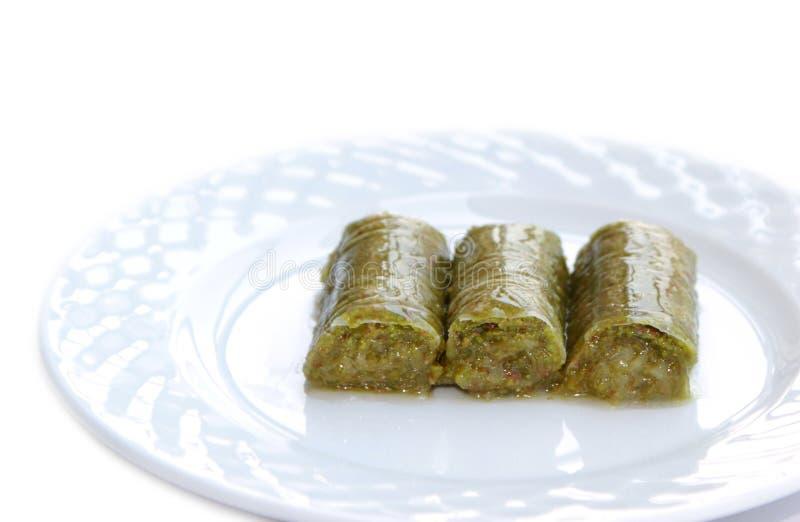 Delicious Turkish sweet, wrapped green pistachio nuts ( Sarma ). On white background stock photo