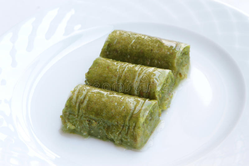 Delicious Turkish sweet, wrapped green pistachio nuts ( Sarma ). On white background stock photography