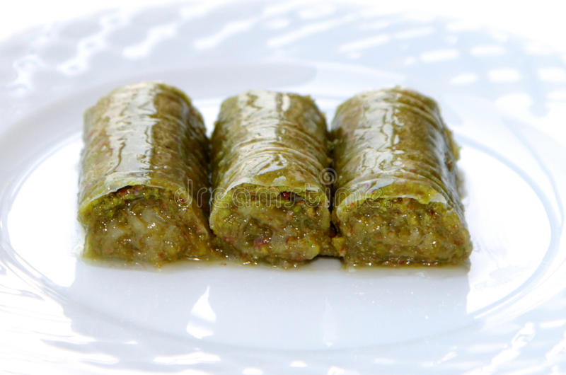 Delicious Turkish sweet, wrapped green pistachio nuts ( Sarma ). On white background royalty free stock images