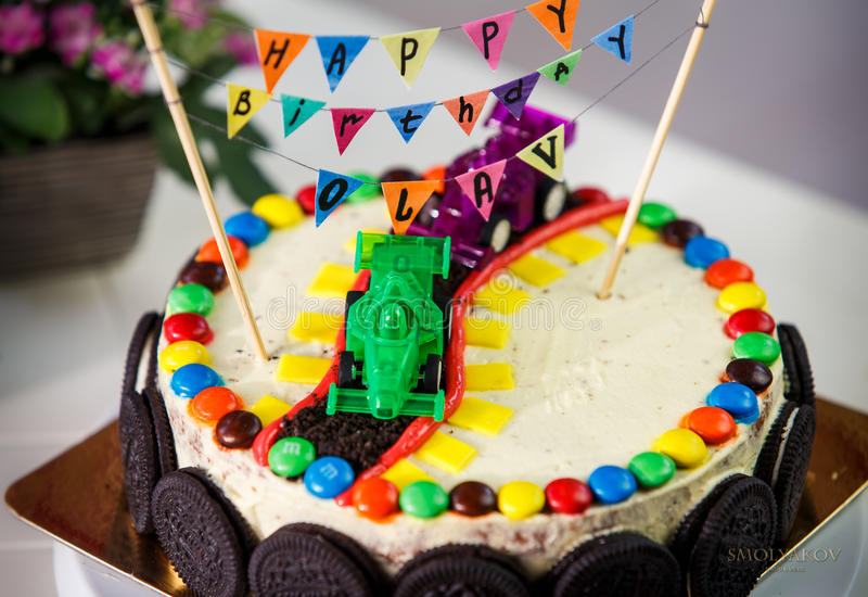 Delicious vanilla cake for children birthday party. Decorated with toys sport cars and chocolate cookies royalty free stock photos