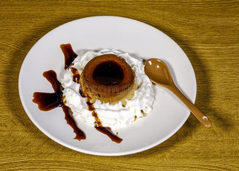 Egg custard with caramel sauce. Delicious vanilla cream, egg custard with caramel sauce, and spoon. Cream bordering stock photo
