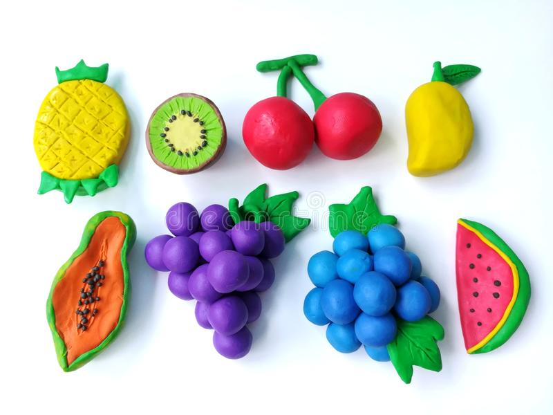 Delicious variety fruits plasticine clay, white background, colorful grapes blueberry shape dough. Delicious variety fruits made from plasticine clay on white royalty free stock photos