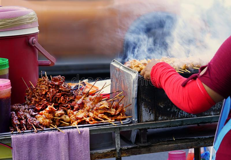 Variety meat grilled with chili sauce on street food stall. Vendor meat roasted to heat. stock photography