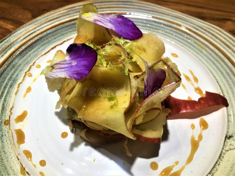 Delicious vegan dessert, apple and flowers by chef Xavi Pellicer. Beautiful woodden table, art, decoration, healthy food, good taste and enchanting decoration royalty free stock photos