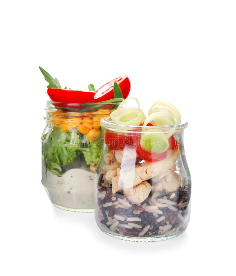 Delicious vegetable salads with chicken in mason jars on white background royalty free stock photos
