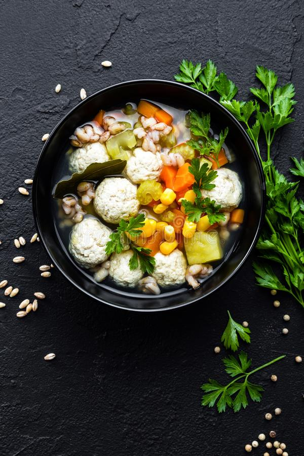 Delicious vegetable soup with chicken meatballs and pearl barley stock image