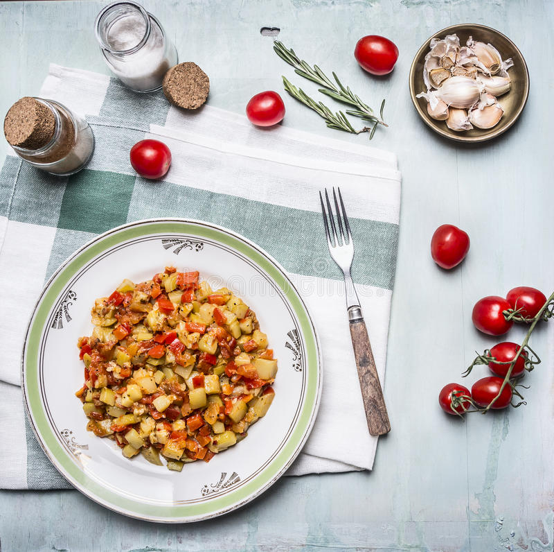 Delicious vegetable stew in a white plate with a fork, with spices, garlic and tomatoes on a branch, on a napkin on blue wooden ru. Delicious vegetable stew a stock image