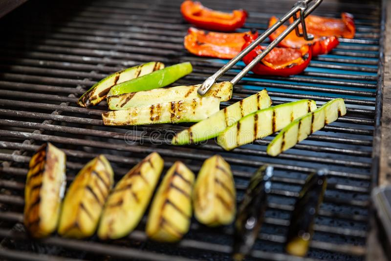 Delicious vegetables grilling in open grill, outdoor kitchen. food festival in city. tasty food peppers zucchini roasting on baske royalty free stock photo
