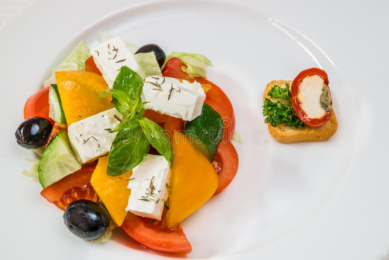 Delicious vegetarian salad from tomatoes, cucumbers, peppers, olives and cheese on a white plate. Horizontal frame stock image