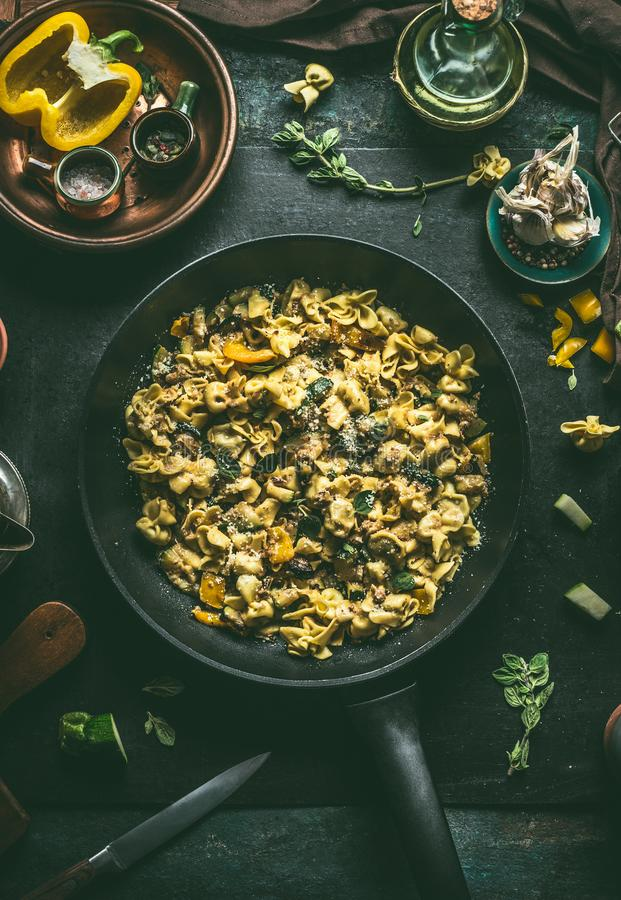 Delicious vegetarian tortellini pasta pan with vegetables, herbs and mushrooms  on plate with fork on dark rustic table background royalty free stock photos