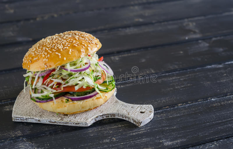 Delicious veggie burger on a dark wooden surface. Healthy breakfast. Or snack stock photography