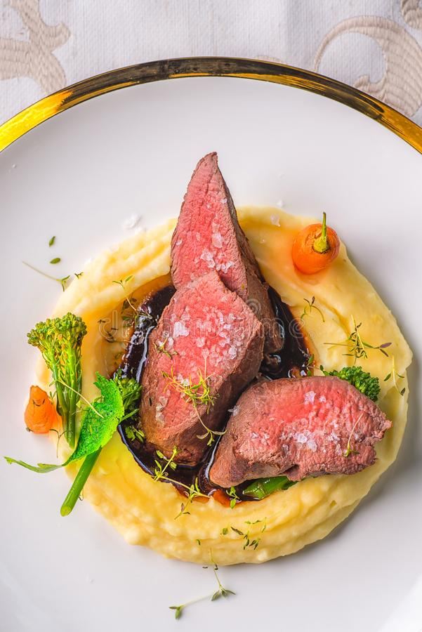Delicious venison steak with potatoes mash and vegetables on white plate, product photography for exclusive restaurant.  royalty free stock image