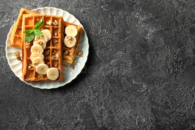 Delicious waffles with banana slices and nuts on grunge background stock photo