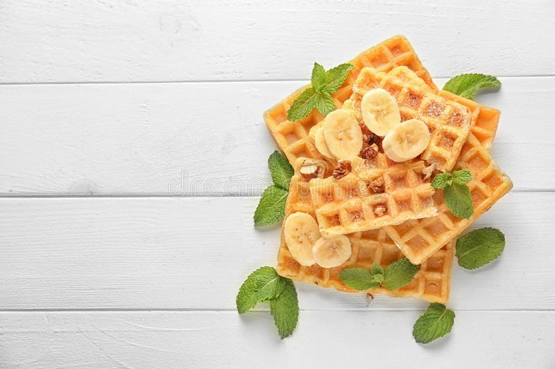 Delicious waffles with banana slices on white wooden table royalty free stock images