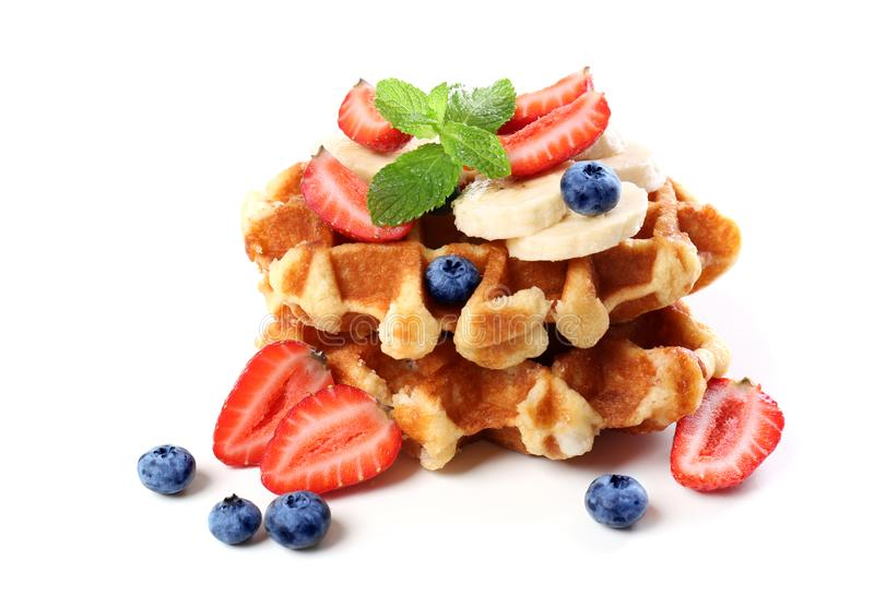 Delicious waffles with berries and banana on white background royalty free stock images