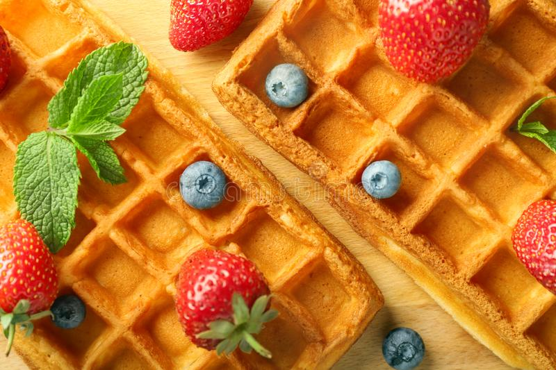 Delicious waffles with berries on wooden board, closeup royalty free stock images