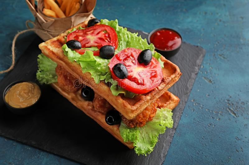Delicious waffles with chicken and vegetables on slate plate royalty free stock images