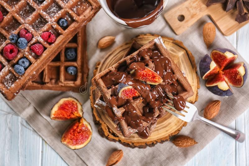 Delicious waffles with fig slices and chocolate sauce on wooden board royalty free stock photos