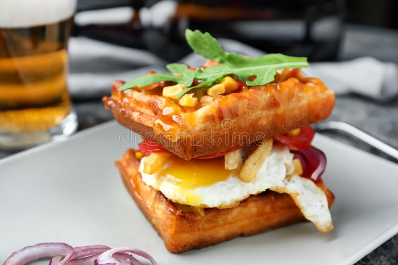 Delicious waffles with fried egg on plate, closeup stock photo