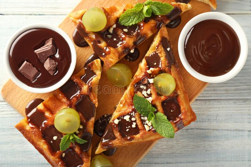 Delicious waffles with grapes and chocolate sauce on wooden board stock images