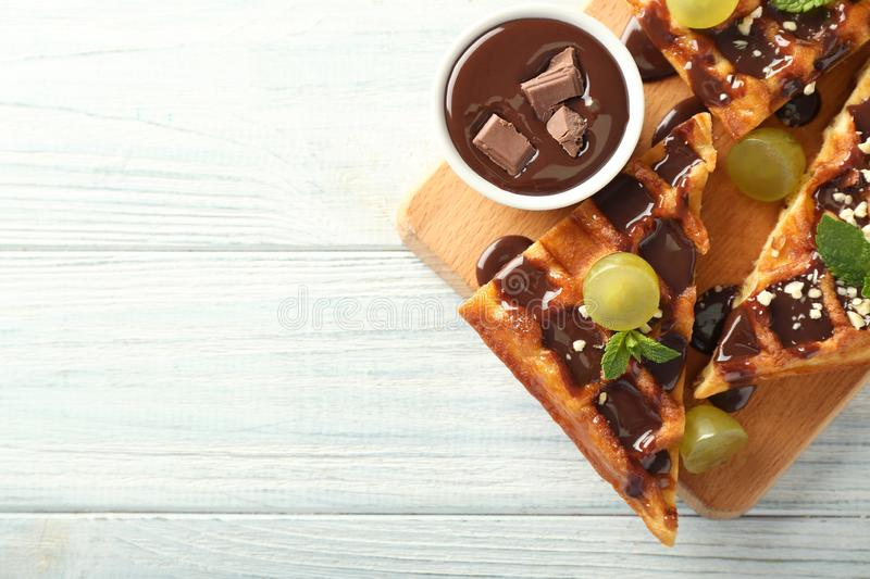 Delicious waffles with grapes and chocolate sauce on wooden table royalty free stock photos