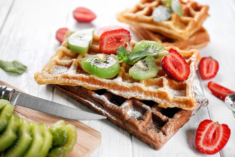 Delicious waffles with kiwi slices and strawberry on white wooden table royalty free stock photography