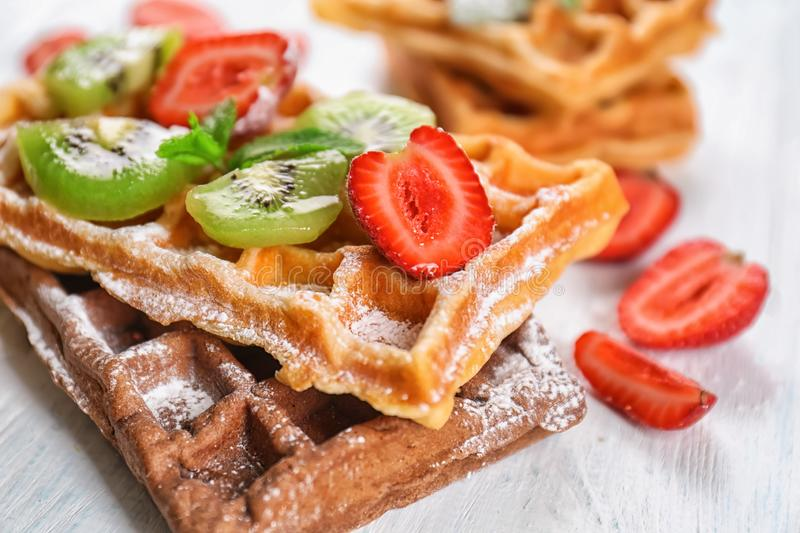 Delicious waffles with kiwi slices and strawberry on white wooden table royalty free stock photo