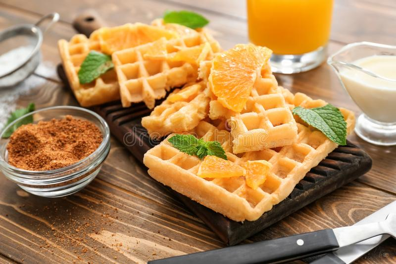 Delicious waffles with orange slices on wooden table stock image