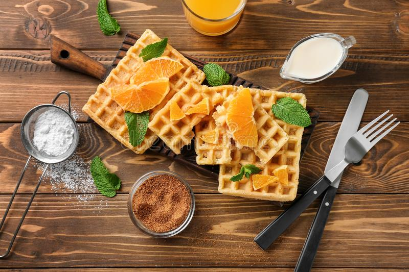 Delicious waffles with orange slices on wooden table royalty free stock photography