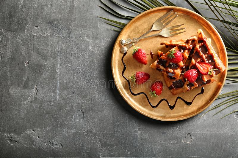 Delicious waffles with strawberries and chocolate sauce on metal tray royalty free stock photography