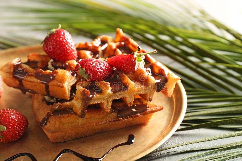 Delicious waffles with strawberries and chocolate sauce on metal tray royalty free stock images
